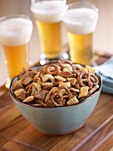 A bowl of snacks with glasses of beer in the background