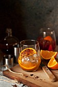 A negroni with spices and roasted oranges being made