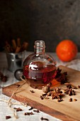 A bottle of spiced gin with star anise and nutmeg on a wooden board