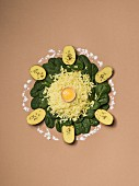 Kartoffeln, Spinat & Eigelb kreisförmig auf braunem Untergrund arrangiert
