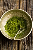 Matcha tea powder in a metal bowl with a spoon