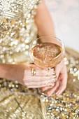 Frau hält ein Glas rosa Weihnachtspunsch