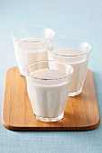 Three glasses of milk on a chopping board