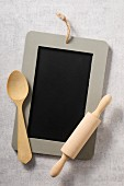 A chalkboard, a wooden spoon and a rolling pin