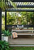 Moderne Terrasse mit Tisch- und Bankgarnitur unter Pergola mit Lamellen Abdeckung