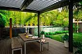 Moderne Holzterrasse unter Pergola mit Lamellen Abdeckung und Tisch- Bankgarnitur, im Hintergrund Pool im Garten