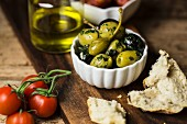 Herb olives, caper fruits, tomatoes and bread