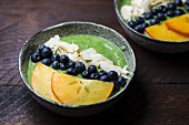 Green smoothies in bowls with blueberries, coconut flakes and persimmon slices