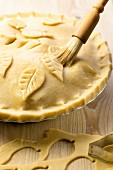 Apple Pie zubereiten: Teigdeckel mit Teigblättern verzieren
