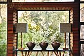 Ablagetisch mit Metallschüsseln und Tischleuchten dekoriert vor Panoramafenster mit Naturblick