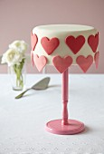 A cake decorated with overhanging hearts for Valentine's Day (Madeira cake)