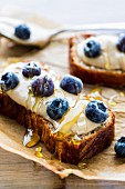 Bread topped with cashew nut butter, blueberries and honey