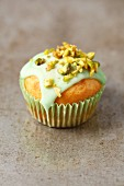 A pistachio cupcake with green icing and chopped pistachio nuts