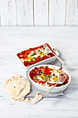 Oven-baked eggs in tomato sauce with peppers and tortillas