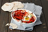 Oven-baked eggs in tomato sauce with peppers served with tortillas