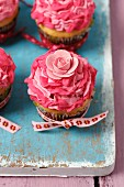 Vanilla cupcakes with pink mascarpone cream and decorative flowers