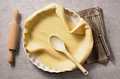 Pastry in a tart dish with a wooden spoon