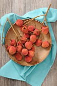 Lychees on twigs on a wooden plate