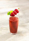 A raspberry and avocado smoothie with orange juice and dried mulberries