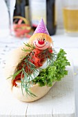 A salmon roll with egg, lettuce and dill, decorated with a clown face