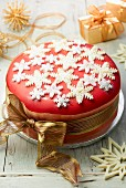 Christmas cake decorated with sugar snow flakes and a gold ribbon