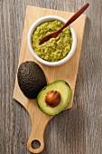 Guacamole and a fresh avocado on a chopping board