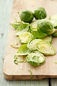 Fresh Brussels sprouts, partially sliced, on a wooden board