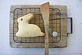 A baked Easter bunny biscuit with a quail egg and a sprig of thyme