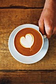 A cappuccino with a heart-shaped milk foam pattern