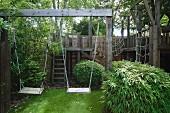 Schaukelanlage aus Holz mit Klettergerüst in sommerlichem Garten