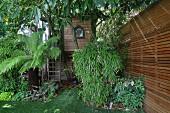 Garten mit Palme und Bambus vor Outdoor-Spielhaus