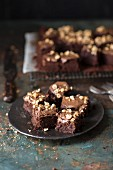 Brownies with nuts on a plate and on a cooling rack