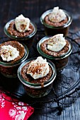 Little chocolate cakes in glasses topped with cream