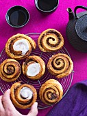 Homemade cinnamon buns with icing on a cooling rack