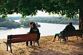 Couples sitting on park benches in Belgrade, Serbia