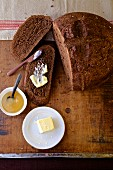 Chocolate bread with butter and honey on a wooden table