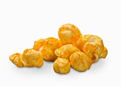 Cheddar popcorn on a white surface (close-up)