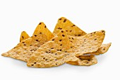Multi-grain tortilla chips with flaxseeds on a white surface