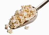 A scoop of popcorn on a white surface (close-up)