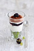 A layered dessert with mascarpone cream, blackberries and grapes