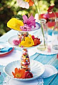 A tiered stand made of plates and bottles filled with colourful sweets, decorated with fresh flowers on a summery set table