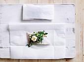 Rohes Fischfilet mit Oliven-Zitronen-Salsa auf Papier