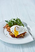 A potato fritter with a poached egg and rocket