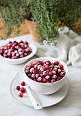 Frozen cranberries in white bowls