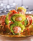 Scampi wrapped in bacon with lettuce leaves