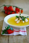 Clear tomato soup with semolina dumplings and fresh herbs