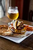 Cheeseburger mit Speck und gegrillten Bananen, Süsskartoffelchips und Glas Bier