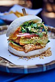 A chicken burger with avocado and radishes