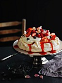 Pavlova with strawberries, blueberries and rose petals