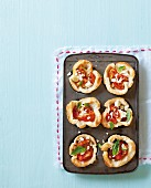 Bread bowls with tomato and feta cheese in a muffin tin